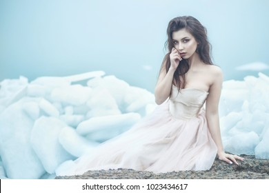 Young beautiful model in luxurious strapless corset ball gown sitting on slabs of broken ice at the misty seaside, her hand at her lips. Winter fairytale concept. Copy space
