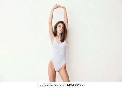 Young beautiful model with natural makeup and beautiful hair on a white background in a light bodysuit