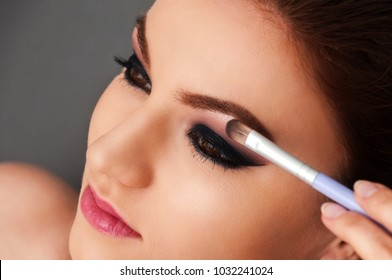 Young beautiful model with pink lipstick and professional make up and cosmetic brush near her eye on the close up shot on the grey background