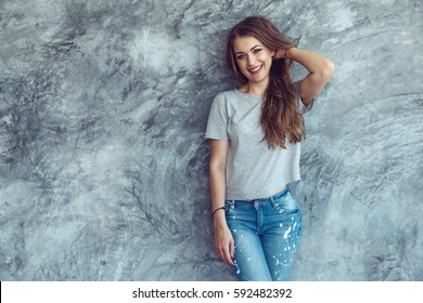 Young beautiful model wearing blank gray t-shirt and jeans posing against rough concrete wall, minimalist street fashion style