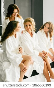 Young beautiful models sit on the bed in white coats