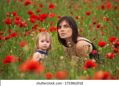 Young beautiful mom with a cute little blonde girl with blue eyes talking in a poppy field. Summer, vacations, travel with children. Blooming poppies in the countryside.