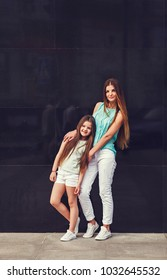 Young beautiful mom with her daughter wearing t-shirt and jeans posing against concrete wall, minimalist street fashion style, clothing for parent and child.