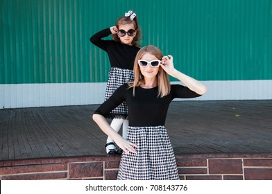 Young beautiful mom with her daughter posing against wall, minimalist street fashion style, family same look, clothing for paren