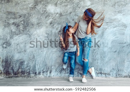 a0636b85a3bf5 Young beautiful mom with her daughter wearing blank gray t-shirt and jeans  posing against