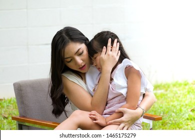Young beautiful mom hugging and comforting daughter from falling run and cry inside the front yard. Asian mothers showing their protection. Concepts of protecting the kid.