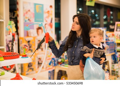 Young beautiful mom with son in baby shop.