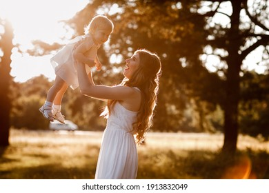 young beautiful mom is walking with little daughter in the sunny park . The concept of summer holiday outdoors. Mother's, baby's day. Spending time together. Sun light