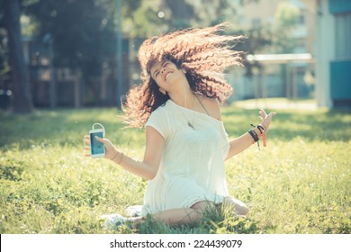 young beautiful moroccan curly woman listening music with smartphone at the park