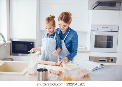 A young and beautiful mother in a blue shirt and apron is preparing dinner at home in the kitchen, along with her little cute daughters with light hair