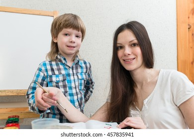 Young beautiful mother with boys son paint colors at home. Mom teaches son to paint colors.