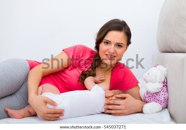 Young beautiful mother breastfeeding her baby on the bed, looking to the camera.