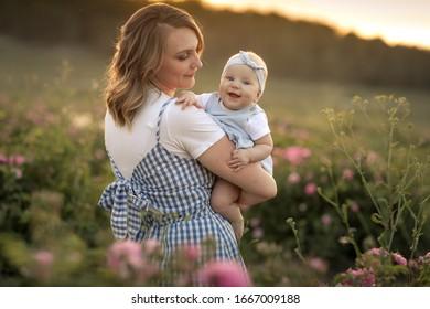Jeune belle mère avec un enfant se dresse dans un champ agricole avec une rose fleurie.