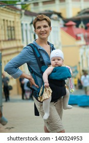 Young beautiful mother with a child walking around the city