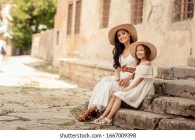 Jeune belle mère d'apparence orientale se promène avec sa fille dans les rues anciennes de la ville méditerranéenne.