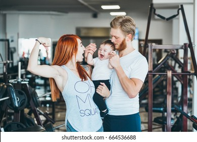 Young beautiful mother and father having fun embracing their cute little boy in gym.