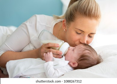 young, beautiful mother is feeding her cute baby daughter with a small bottle, filled with milk