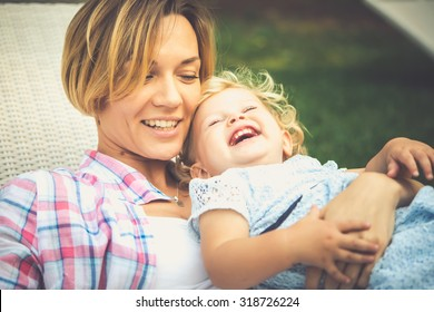 Young beautiful mother has fun with her daughter during a walk outdoors. Toned image