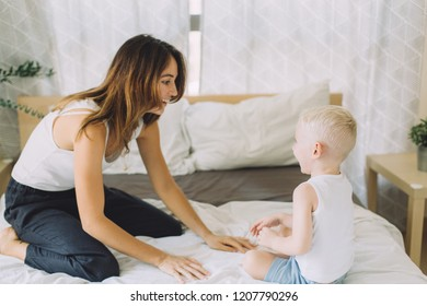 young beautiful mother having fun with her son in bedroom at home
