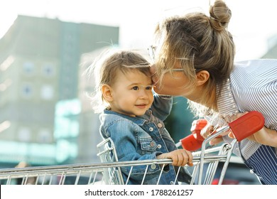 Young beautiful mother and her cute little son in a shopping cart  beside a supermarket