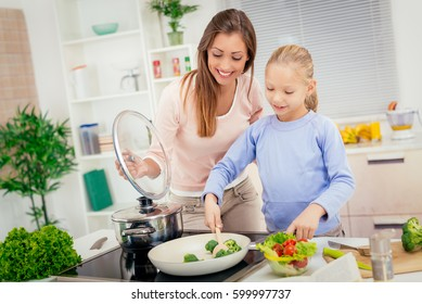 Young beautiful mother and her cute daughter cooking healthy meal in the kitchen.