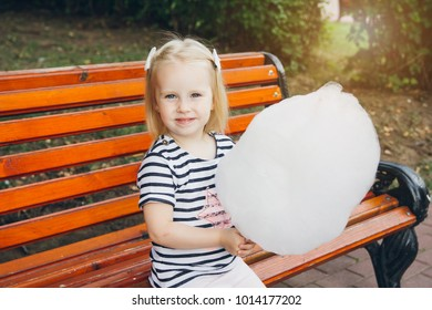 Young beautiful mother and her little daughter eating cotton candy in the Park in the summer. The concept of family recreation. Toning.