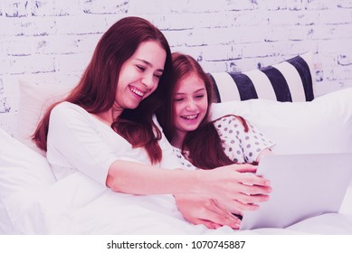 Young beautiful mother with her little girls using a laptop searching internet. Mom and daughter watching cartoon from laptop in the bedroom.