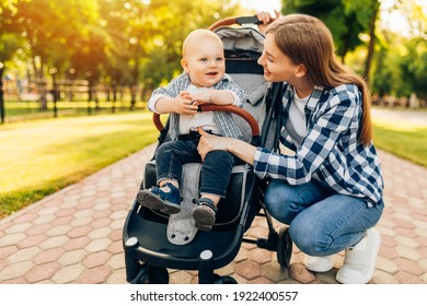 Young beautiful mother, with her little cute child, walking in the park on a sunny summer day.