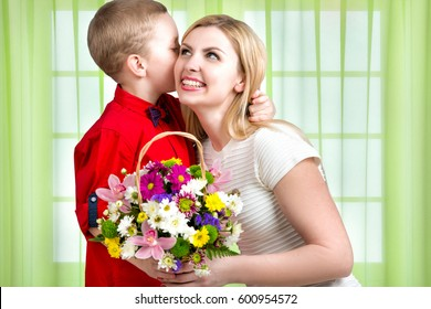 Young beautiful mother with her son.To whisper a secret in your ear.       Woman and child with bouquet of flowers. Spring family holiday concept. Women's day.