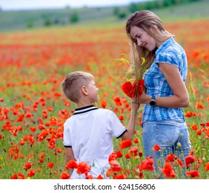 Young beautiful mother with her son walking in poppy field