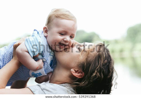 Young beautiful mother holding cute little baby boy smiling