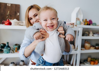 Young and beautiful mother holding on her hangs her sweet little baby son. Shot against a shelf filled with clay utensils.