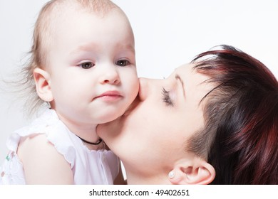 Young beautiful mother kissing cute curious baby, family portrait