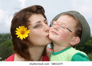 Young beautiful mother kissing her son,background nature