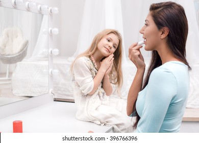 Young beautiful mother and little daughter while applying makeup. Nice cozy bedroom. Daughter looking at mother and smiling