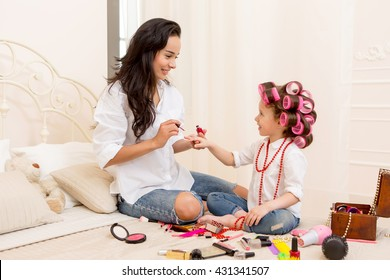young beautiful mother paints her nails her pretty daughter on the bed . Daughter with curlers on her head laughing