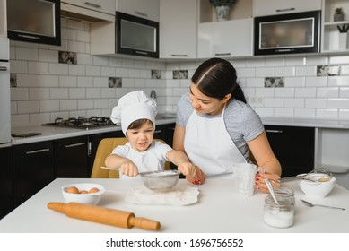 A young and beautiful mother is preparing food at home in the kitchen, along with her little son