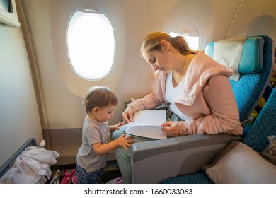 a young beautiful mother sits in an airplane chair and reads a book to her little cute toddler, who is standing in front of her. close-up, soft focus, top view.  place for copyspace, empty page