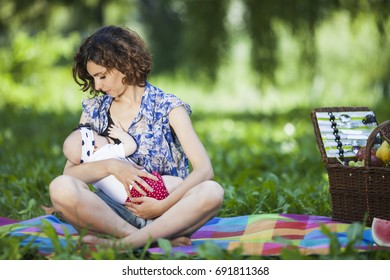 Young beautiful mother sits on blanket with her daughter during a picnic in the park