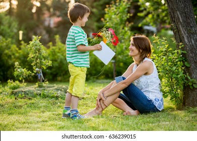 Young beautiful mother, sitting in a garden, little boy, her son, bringing gerbera flowers and present for her, mothers day surprise