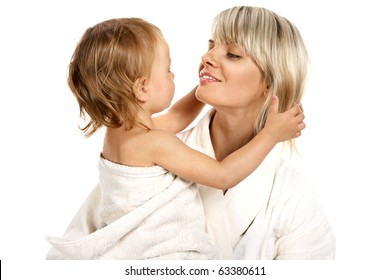 Young beautiful mother and small daughter after bathing sitting in towels.