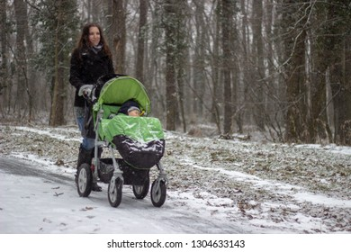 young beautiful mother is smiling and walking with the green stroller with little beautiful adorable son babyboy in it on the footpath covered with snow in the snowy forest