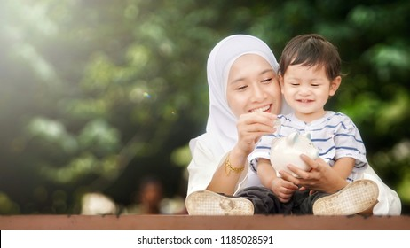 Young beautiful mother and son putting coins into a piggy bank at the park. Money saving concept. Bokeh background with backlight editing to create mood.