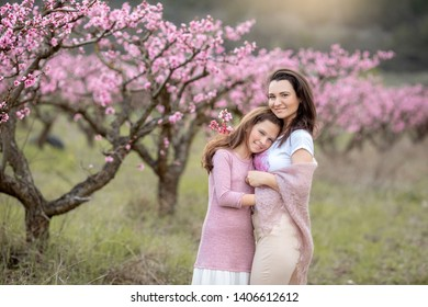 Young Beautiful Mother at Spring, Pink Blooming Tree at the Background