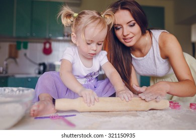 young beautiful mother teaches daughter prepare dough in the kitchen