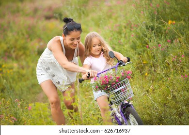Young beautiful mother teaching her little daughter to ride a bike in the field. Mom and cute girl having fun together