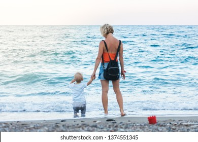 A young and beautiful mother walks in the fresh air on the beach with her young child. The boy squatted down to get a pebble he liked at sunset time. The concept of a happy family, lifestyle, vacation