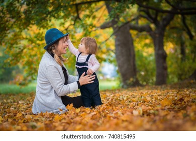Young beautiful mother wearing blue hat having fun with her toddler in autumn forest sitting on leaves