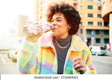 Young beautiful multiethnic woman outdoors drinking from reusable bottle - ecological, sustainable, no waste concept