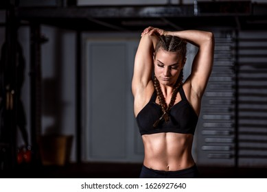 Young beautiful muscular attractive fit girl stretch her hand muscles after heavy hardcore crossfit workout training in the gym close up